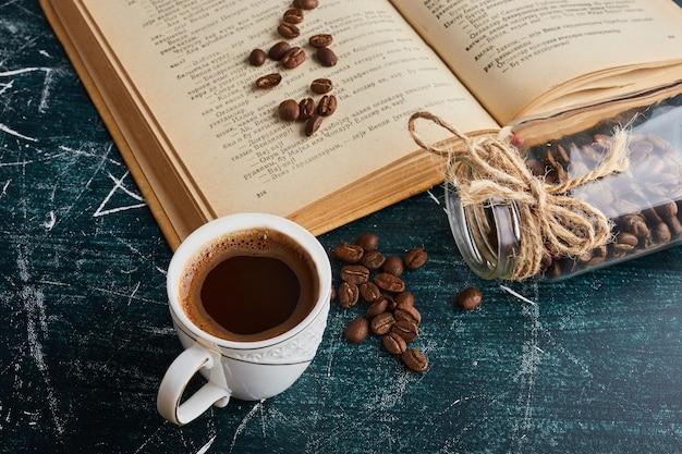 Uma xícara de café com um livro à parte.