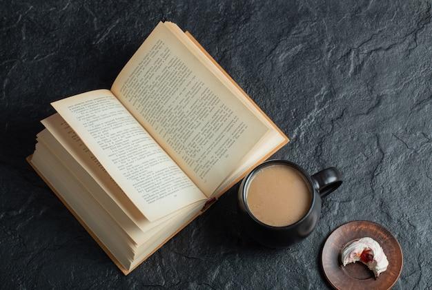 Uma xícara de café com um livro sobre uma superfície escura.