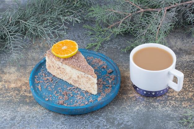 Uma xícara de café com um pedaço de bolo saboroso na placa azul. foto de alta qualidade