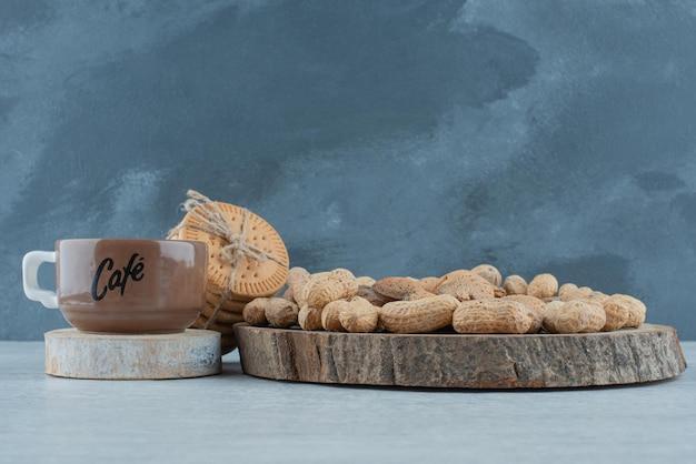 Uma xícara de café com várias nozes e biscoitos