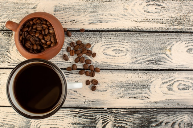 Uma xícara de café com vista de cima com sementes de café marrom na mesa rústica cinza e bebida cor de café