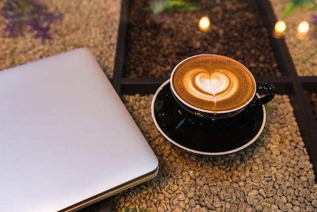 Uma xícara de café de latte art com o computador portátil na mesa com grãos de café