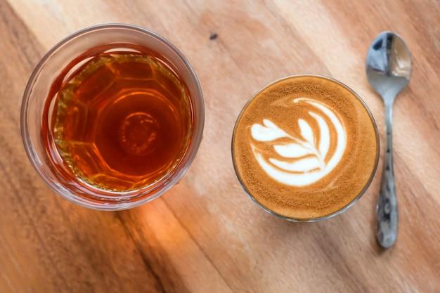 Uma xícara de café de latte art e chá quente na madeira