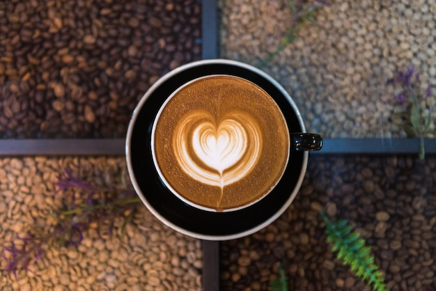 Uma xícara de café de latte art na mesa com origens de grãos de café