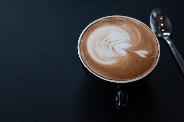 Uma xícara de café de latte art na mesa de madeira escura