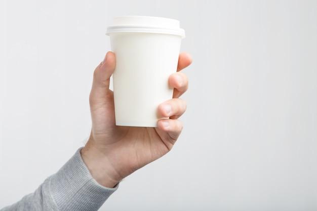 Uma xícara de café de papel na mão. livro branco xícara de café na mão isolada