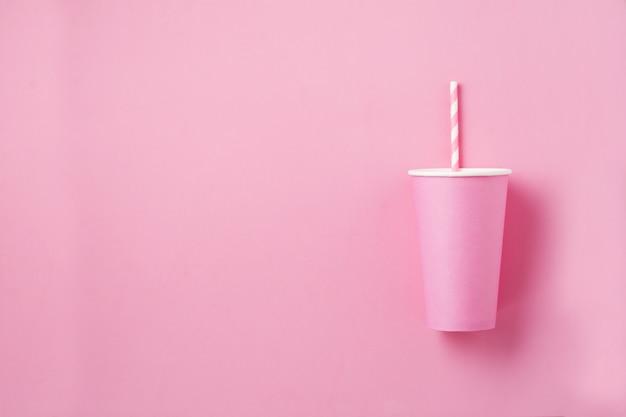 Uma xícara de café de papel rosa na superfície da luz de papel rosa. postura plana.