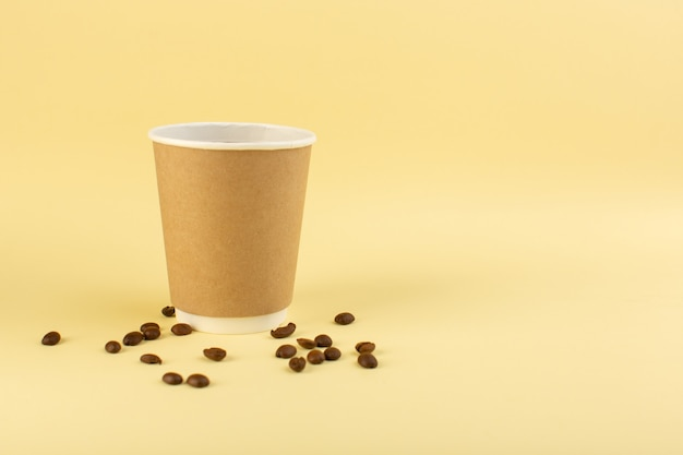 Uma xícara de café de plástico frontal com sementes de café marrom na parede amarela