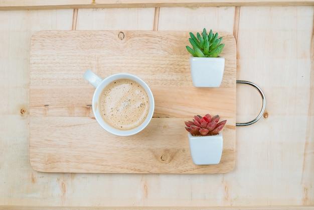 Uma xícara de café doce colocada em uma placa de madeira decorada com duas plantas