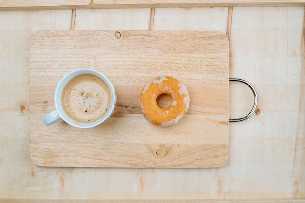 Uma xícara de café doce colocada em uma placa de madeira junto com uma rosquinha.