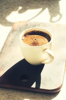 Uma xícara de café e a sombra do bule