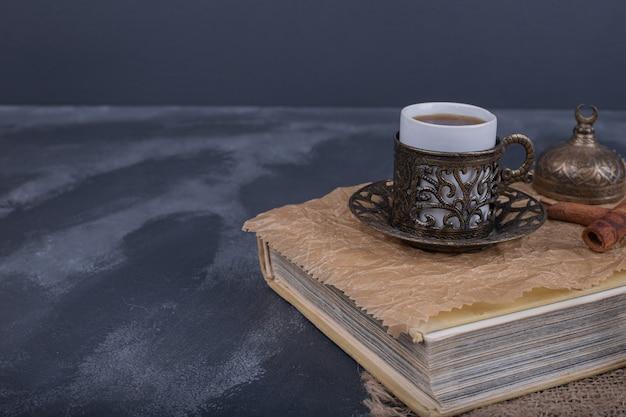 Uma xícara de café e canela em cima do livro.