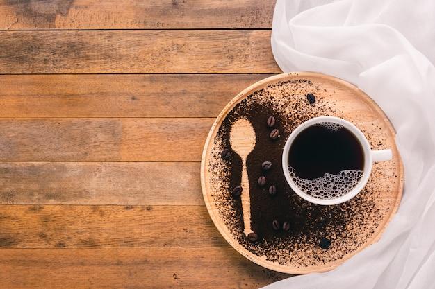 Uma xícara de café e colher de forma na bandeja de madeira, vista superior, com espaço de cópia
