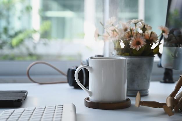 Uma xícara de café é colocar no local de trabalho do fotógrafo em um escritório doméstico moderno.