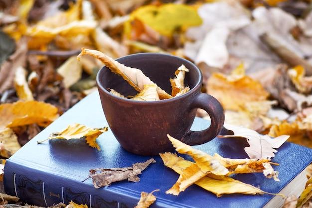 Uma xícara de café e folhas secas e marrons em um livro na floresta de outono