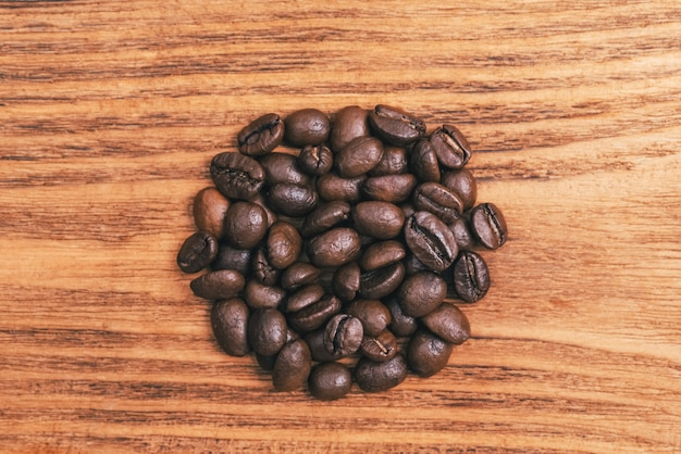 Uma xícara de café e grãos de café espalhados.