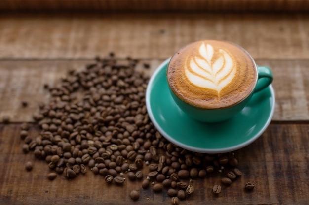 Uma xícara de café e grãos de café na mesa de madeira.