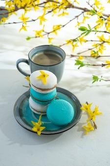 Uma xícara de café e macaroons de cor sobre fundo claro