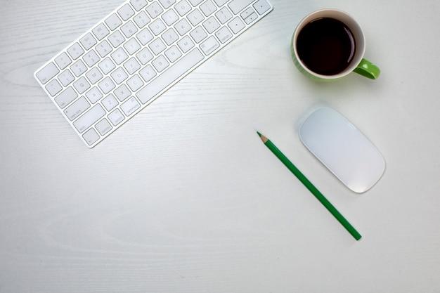 Uma xícara de café e teclado e mouse sem fio