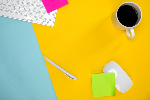 Uma xícara de café e teclado sem fio com o mouse
