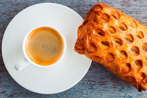Uma xícara de café e um bolo em uma mesa de madeira.