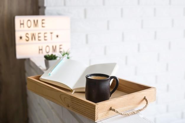 Uma xícara de café e um caderno aberto em uma bandeja de madeira