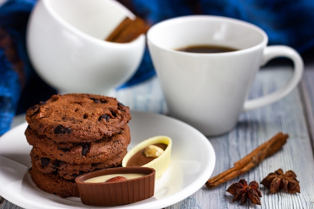 Uma xícara de café e um pires com biscoitos de chocolate e doces em uma mesa branca estilo provençal ...