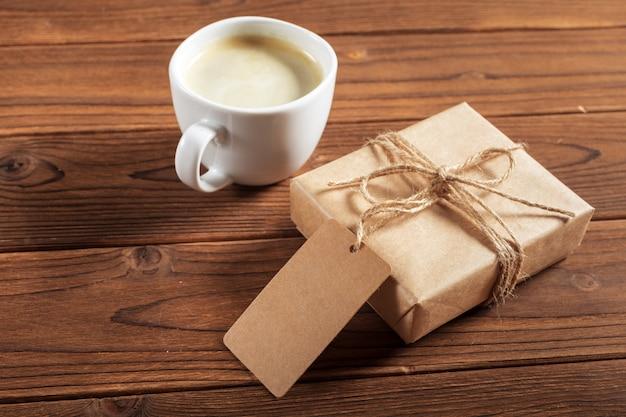 Uma xícara de café e um presente embrulhado em uma mesa de madeira