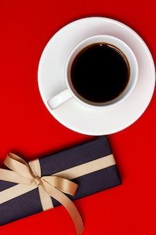 Uma xícara de café e um presente preto com uma fita bege em um fundo vermelho. vista de cima.