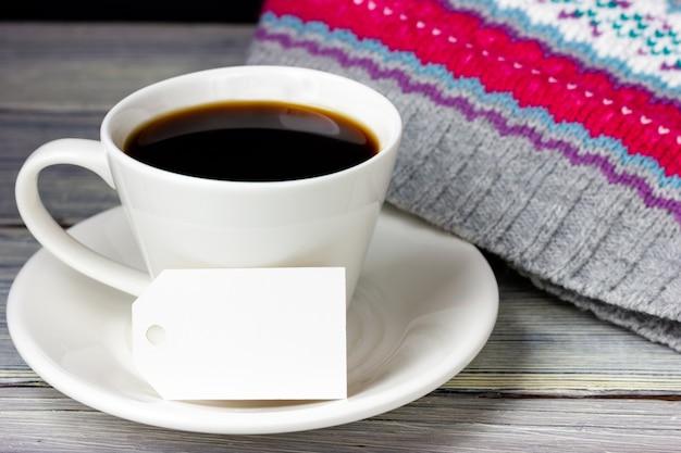 Uma xícara de café e uma etiqueta de papel em branco sobre uma mesa de madeira clara.
