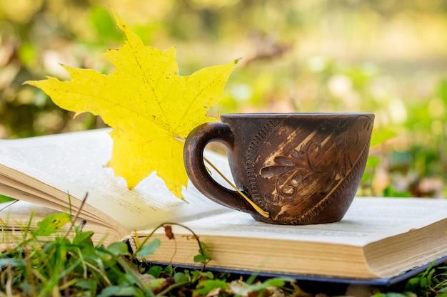 Uma xícara de café e uma folha de bordo amarela em um livro na floresta Foto Premium