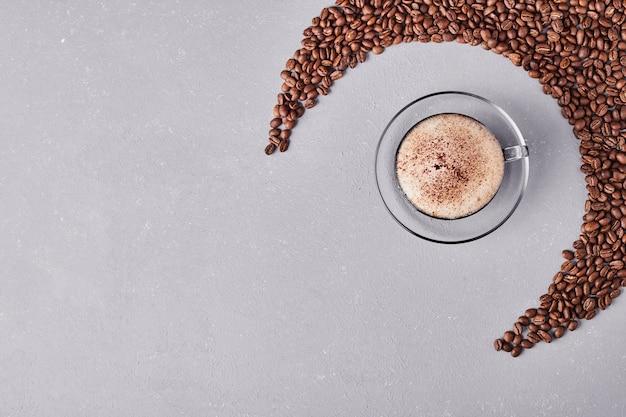 Uma xícara de café em pires de vidro.