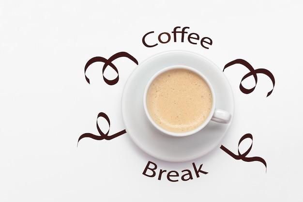 Uma xícara de café em um fundo branco e a vista superior da pausa para o café de inscrição com uma cópia do espaço.