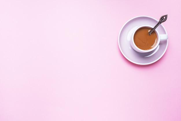 Uma xícara de café em um fundo rosa com espaço de cópia. vista do topo. minimalismo.