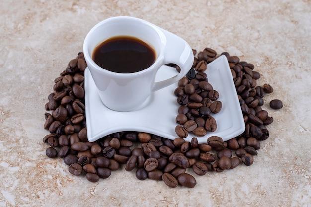 Uma xícara de café em um pires sentado em uma pilha de grãos de café