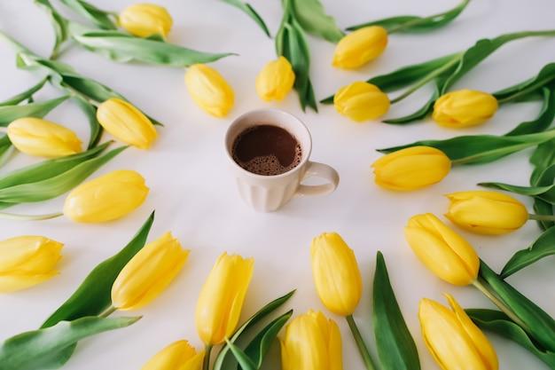 Uma xícara de café em um quadro de tulipas frescas em branco.