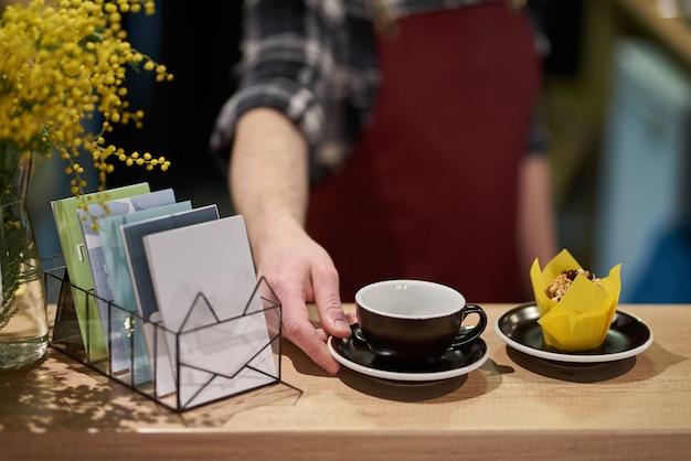 Uma xícara de café em um rack de café com um cupcake, flores de mimosa e calendários ficam nas proximidades.