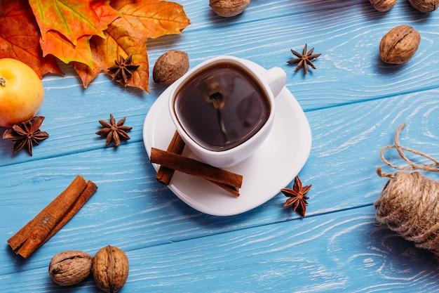 Uma xícara de café em uma mesa azul com maçãs