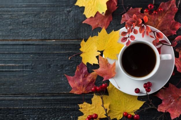 Uma xícara de café em uma mesa com folhas de outono