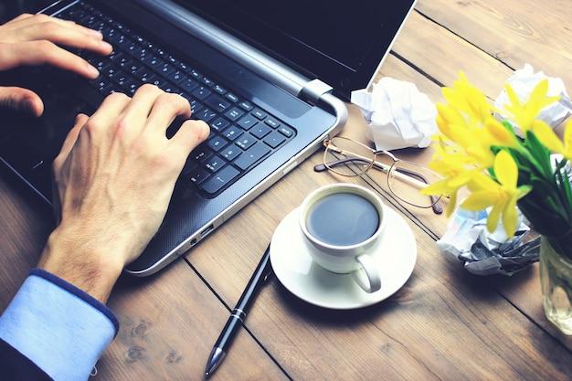 Uma xícara de café em uma mesa de madeira com um homem trabalhando em um laptop