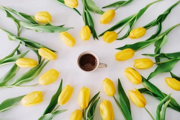 Uma xícara de café em uma moldura de tulipas amarelas em branco.