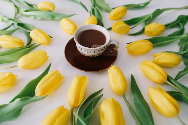 Uma xícara de café em uma moldura de tulipas em branco.