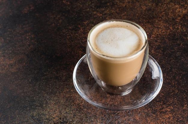 Uma xícara de café em uma xícara branca na mesa de fundo escuro de metal.