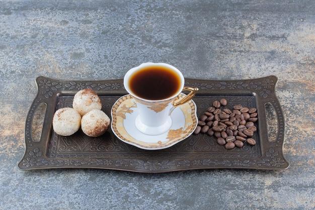 Uma xícara de café escuro com biscoito no quadro escuro. foto de alta qualidade