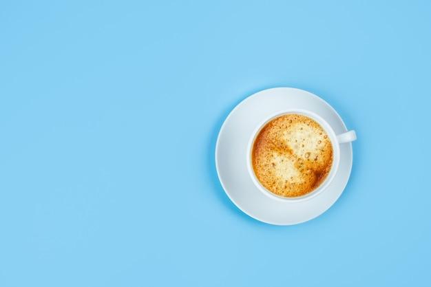 Uma xícara de café expresso branco sobre uma mesa azul.