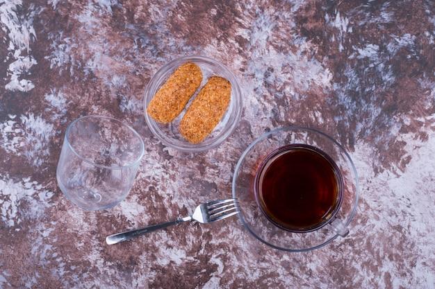 Uma xícara de café expresso com biscoitos de gergelim em um pires de vidro no mármore, vista de cima
