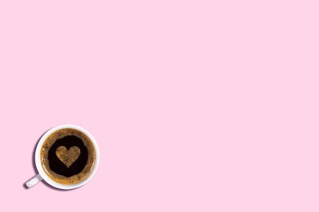 Uma xícara de café expresso com espuma e formato de coração em um espaço de cópia de fundo rosa suave
