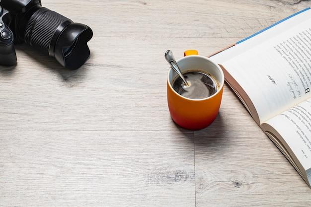 Uma xícara de café expresso com um bom livro e uma câmera fotográfica ao redor