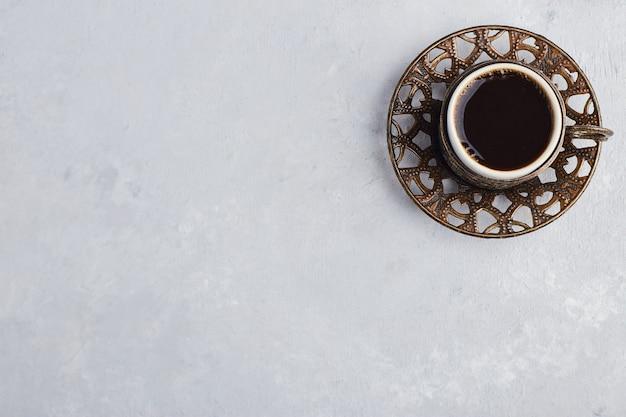 Uma xícara de café expresso em pires metálico.