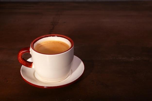 Uma xícara de café expresso em um fundo escuro de madeira